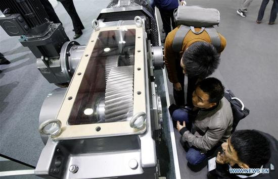 Visitors look at gear box products at the 2017 Power Transmission and Control Asia in Shanghai, east China, Oct. 31, 2017. About 2,500 enterprises from home and abroad participated in the event, which focused on intelligent manufacturing this year. (Xinhua/Fang Zhe)