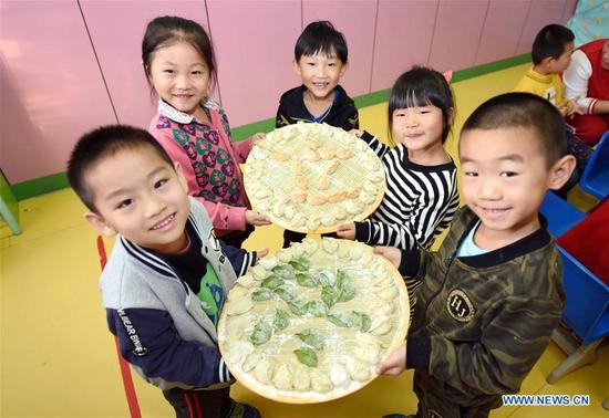 Children show dumplings made by themselves at a kindergarten in Shenzhou, north China's Hebei Province, Nov. 7, 2017, to celebrate the Beginning of Winter, a Chinese traditional solar term that fell on Tuesday this year. (Xinhua/Zhu Xudong)