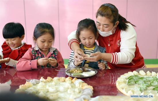Children learn to make dumplings at a kindergarten in Shenzhou, north China's Hebei Province, Nov. 7, 2017, to celebrate the Beginning of Winter, a Chinese traditional solar term that fell on Tuesday this year. (Xinhua/Zhu Xudong)