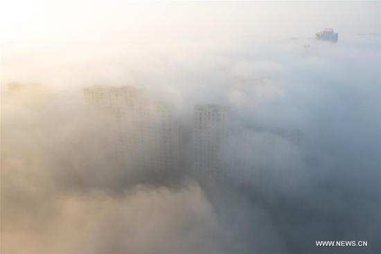 Buildings are enveloped in advection fog in the Shangyu District of Shaoxing City, east China's Zhejiang Province, Nov. 9, 2017. (Xinhua/Weng Xinyang)
