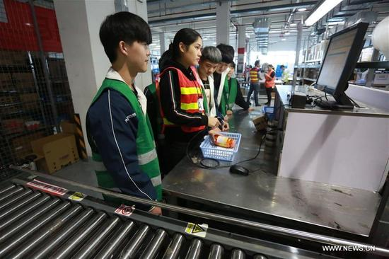 A staff member (2nd L) of a cross-border e-commerce company demonstrates operation procedures to new employees in Ningbo, east China's Zhejiang Province, Nov. 8, 2017. Cross-border e-commerce companies and courier services in Ningbo are busy preparing for the Singles' Day shopping spree which falls on Nov.11. (Xinhua/Huang Ruipeng)