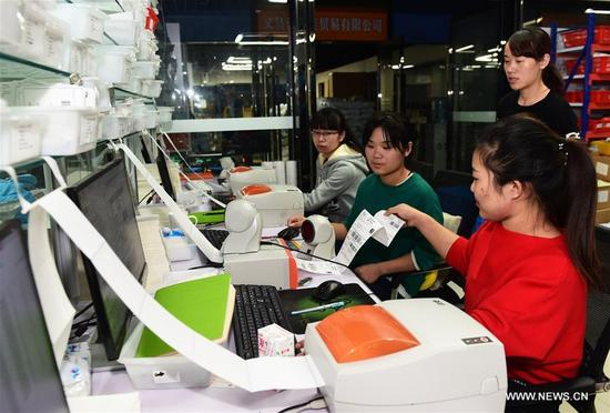 Staff members of an e-commerce company print out courier receipt in Yiwu, east China's Zhejiang Province, Nov. 8, 2017. The e-commerce companies and courier services are busy preparing for the Singles' Day shopping spree which falls on Nov.11. (Xinhua/Gong Xianming)