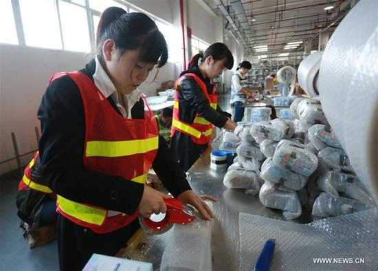 Staff members of a cross-border e-commerce company package products in Ningbo, east China's Zhejiang Province, Nov. 8, 2017. Cross-border e-commerce companies and courier services in Ningbo are busy preparing for the Singles' Day shopping spree which falls on Nov.11. (Xinhua/Huang Ruipeng)