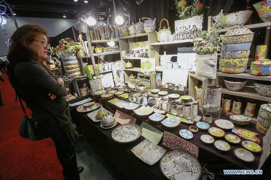 A visitor looks at ceramic crafts displayed at the Circle Craft Market in Vancouver, Canada, Nov. 8, 2017. Over 300 artisans from across Canada participated in the 5-day event to showcase various crafts. (Xinhua/Liang Sen)