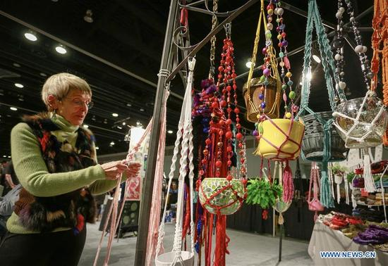 A vendor showcases her knitting crafts at the Circle Craft Market in Vancouver, Canada, Nov. 8, 2017. Over 300 artisans from across Canada participated in the 5-day event to showcase various crafts. (Xinhua/Liang Sen)