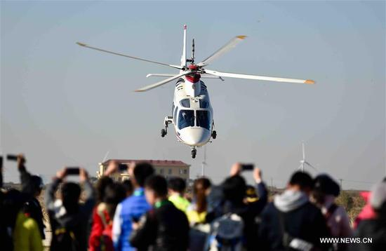 People watch a performance of a helicopter on Douzhuang General Aviation Airport, Binhai District in north China's Tianjin Municipality, Nov. 11, 2017. Tianjin's first aero-sport camp was put into use here on Saturday. (Xinhua/Yue Yuewei)