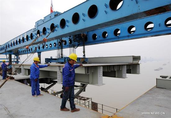 Workers install the last steel bridge deck at the site of a reinforcement project of Jiujiang Yangtze River Bridge in east China's Jiangxi Province, Nov. 12, 2017. Constructors finished installation of steel main girders for the bridge's reinforcement project on Sunday. (Xinhua/Hu Guolin)