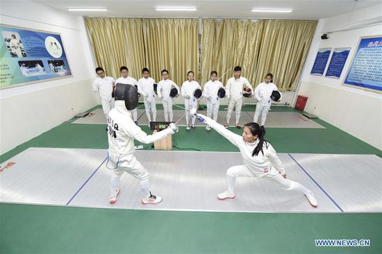 Teacher Guo Jing (R) demonstrates fencing skills to students at No. 34 Middle School in Hohhot, capital of north China's Inner Mongolia Autonomous Region, Nov. 13, 2017. (Xinhua/Wang Zheng)