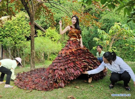A model presents a dress made of leaves to promote environmental protection at the Shampoola scenic area in Fogang County of Qingyuan City, south China's Guangdong Province, Nov. 12, 2017. The dress was made of 5,888 leaves by four staff members in a week. (Xinhua/Cao Jing)