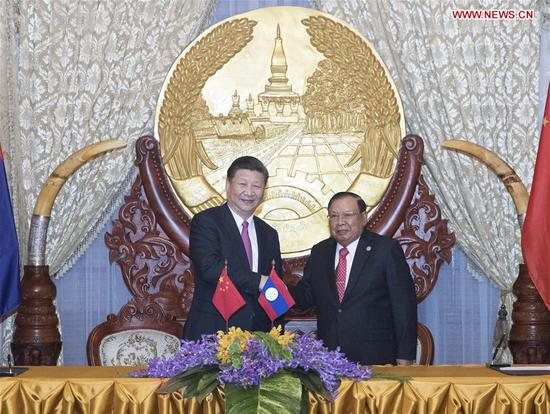 Chinese President Xi Jinping (L), also general secretary of the Communist Party of China Central Committee, shakes hands with Bounnhang Vorachit, general secretary of the Lao People's Revolutionary Party (LPRP) Central Committee and president of Laos, while jointly witnessing the signing of bilateral cooperation documents after their talks in Vientiane, Laos, Nov. 13, 2017. (Xinhua/Wang Ye)