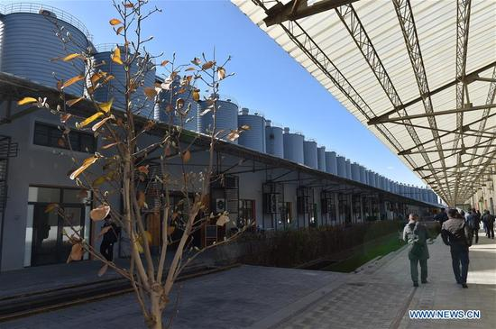 People visit a cultural and creative industrial park in Beijing, capital of China, Nov. 13, 2017. The park was transformed from a concrete storage area, with the old warehouses and railway facilities preserved. So far, more than 80 cultural and creative companies have started business in the park. (Xinhua/Luo Xiaoguang)