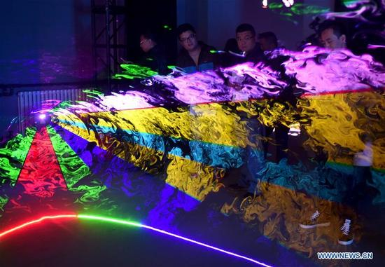 People watch a laser show at a cultural and creative industrial park in Beijing, capital of China, Nov. 13, 2017. The park was transformed from a concrete storage area, with the old warehouses and railway facilities preserved. So far, more than 80 cultural and creative companies have started business in the park. (Xinhua/Luo Xiaoguang)