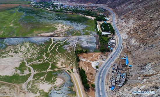 Photo taken on May 11, 2017 shows the highway which runs near Lalu wetland in Lhasa, southwest China's Tibet Autonomous Region. Highways have been built to improve transportation in Tibet. (Xinhua/Purbu Zhaxi)