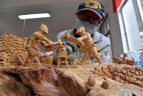 A participant works on a root sculpture at the 2017 Chinese skill competition - national carving vocational skill contest final - in Yujiang County, east China's Jiangxi Province, Nov. 13, 2017. A total of 117 people from 11 provinces attended the competition aimed at promoting craftsmanship spirit. (Xinhua/Peng Zhaozhi)