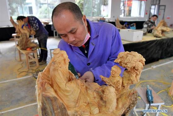 Contestants work on the root sculpture at the 2017 Chinese skill competition - national carving vocational skill contest final - in Yujiang County, east China's Jiangxi Province, Nov. 13, 2017. A total of 117 people from 11 provinces attended the competition aimed at promoting craftsmanship spirit. (Xinhua/Peng Zhaozhi)