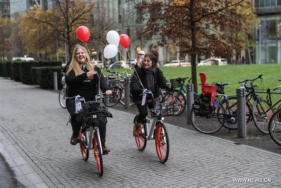 Staff members ride bikes of Chinese bike-sharing company Mobike in Berlin, capital of Germany, on Nov. 21, 2017. Chinese bike-sharing company Mobike on Tuesday launched its service with 700 bikes in Berlin, the first city in Germany and the 200th city around the world. (Xinhua/Shan Yuqi)