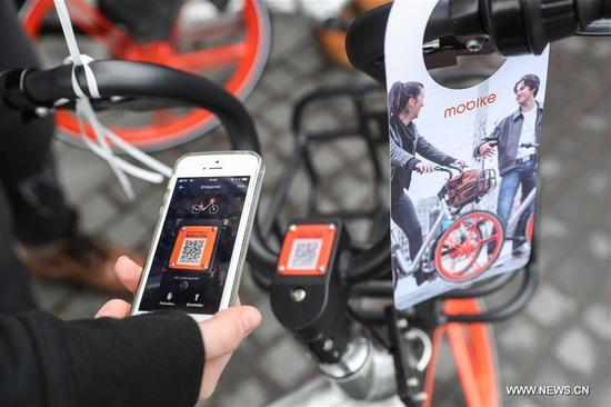 A staff member unlocks a bike of Chinese bike-sharing company Mobike by scanning the QR Code in Berlin, capital of Germany, on Nov. 21, 2017. Chinese bike-sharing company Mobike on Tuesday launched its service with 700 bikes in Berlin, the first city in Germany and the 200th city around the world. (Xinhua/Shan Yuqi)
