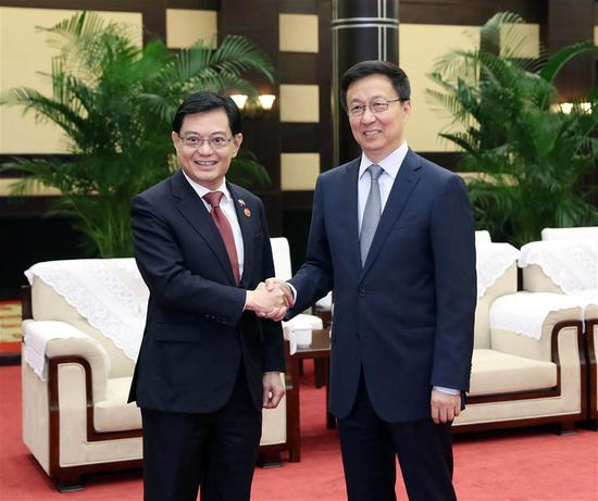 Chinese Vice Premier Han Zheng, also a member of the Standing Committee of the Political Bureau of the Communist Party of China Central Committee, meets with Singaporean Deputy Prime Minister Heng Swee Keat in southwest China's Chongqing, Oct. 15, 2019. (Xinhua/Liu Weibing)