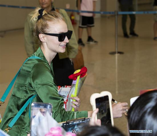 Actress Sophie Turner signs for fans upon her arrival to promote the film