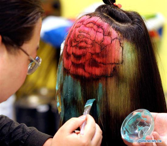 A hairdresser applies dye to a model's hair in Luoyang, central China's Henan Province, April 30, 2005. Along with China's reform and opening-up starting from 1978, Chinese women have refreshed their images year after year, which can be simply seen from their hairstyles. Women's hairstyles, just like a mirror, reflect fashion changes and most importantly, Chinese women's increasingly diversified definition of beauty. (Xinhua/Zhang Xiaoli)
