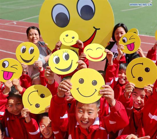 Pupils demonstrate smiley cards to greet the upcoming World Smile Day at a primary school in Qinhuangdao, north China's Hebei Province, May 7, 2019. World Smile Day is celebrated on May 8 every year. (Xinhua/Cao Jianxiong)