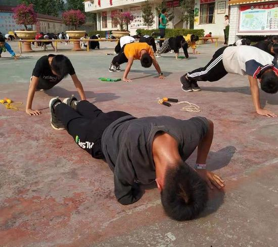 Zhang Jiacheng is doing push-ups with classmates at his school.