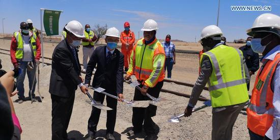 Officials from Namibian Ministry of Works and Transport and China Gezhouba Group Corporation in Namibia break ground for the project of the rehabilitation and upgrading of the railway line between Walvis Bay and Arandis in Arandis, western Namibia, on Nov. 30, 2020. The Namibian government's plan to develop the country into a transport and logistics hub in southern Africa helped by the groundbreaking of the rehabilitation and upgrading of the railway line between Walvis Bay and Arandis on Monday. The project will be undertaken by China Gezhouba Group Corporation (CGGC) in Namibia and the development is set to enhance 70 percent of the railway network, and make the railway transportation meet the railway transport capacity of the Southern African Development Community (SADC). (Photo by Sun Yumo/Xinhua)