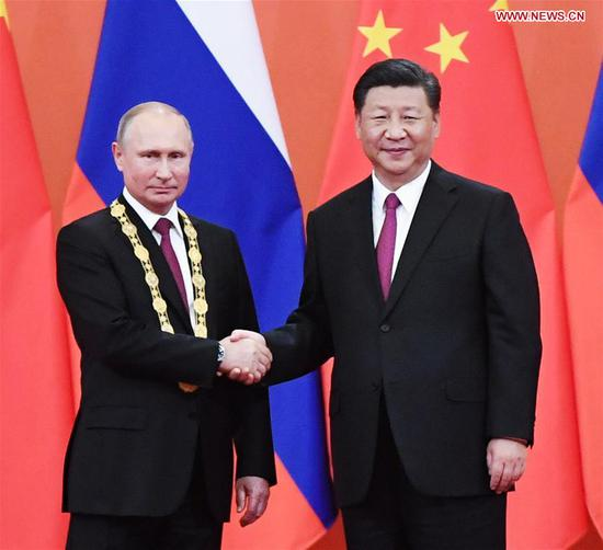 Chinese President Xi Jinping awards his Russian counterpart Vladimir Putin the first-ever Friendship Medal of the People's Republic of China at the Great Hall of the People in Beijing, capital of China, June 8, 2018. (Xinhua/Shen Hong)