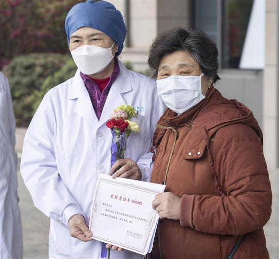 Li Lanjuan (L), a renowned Chinese epidemiologist, poses for a photo with the 600th cured patient of COVID-19 at the east branch of Renmin Hospital of Wuhan University in Wuhan, central China's Hubei Province, March 16, 2020. The 600th patient confirmed of novel coronavirus infection has been discharged from the east branch of the hospital on Monday. (Xinhua/Cai Yang)