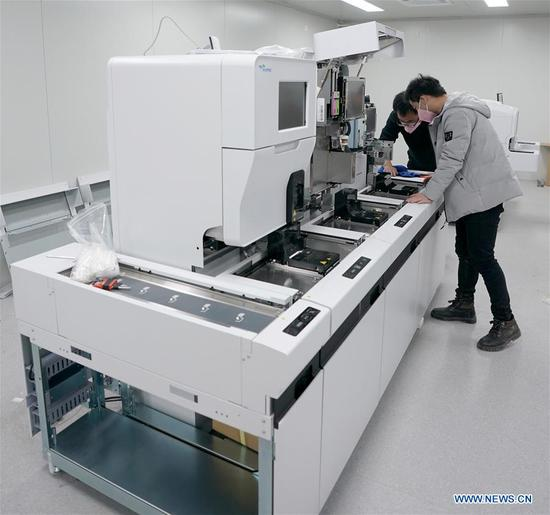 Technicians test the urine analyzer at the Leishenshan (Thunder God Mountain) Hospital which is under construction in Wuhan, central 四不像心水's Hubei Province, Feb. 5, 2020. Leishenshan Hospital, one of the makeshift hospitals to battle against the novel strain of coronavirus in Wuhan, has completed its main part of construction. (Xinhua/Wang Yuguo)