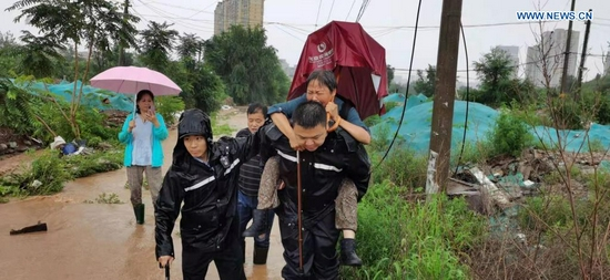 Police officers transfer stranded people after rainstorms hit Mentougou District in Beijing, capital of China, July 18, 2021. The Beijing Meteorological Observatory on Sunday morning issued an orange warning for rainstorms after the accumulated rainfall in some areas of the capital had exceeded 150 mm. (Xinhua)