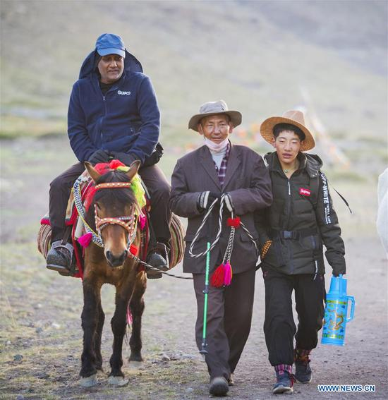A villager (C) from Gangsha Village offers services to a pilgrim in Ali Prefecture, southwest China's Tibet Autonomous Region, June 26, 2018. Gangsha Village is located at the foot of Mount Kangrinboqe, a sacred Hindu and Buddhist site in Ali. Since the 1980s, local farmers and herdsmen have started to receive pilgrims and tourists from home and abroad. They upgraded services of tourism industry in the past 30 years, and tourism increased villagers' income. (Xinhua/Liu Dongjun)