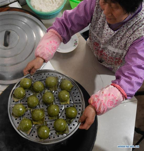A villager shows steamed Qingtuan, or green sticky rice balls, in Yiyanshan Village of Huzhou, east China's Zhejiang Province, April 4, 2019. Qingtuan, made from glutinous rice mixed with wormwood juice and stuffed with bamboo shoot, tofu and preserved meat, is a traditional snack popular mailnly among people living in the south of Yangtze River during the Qingming Festival also known as Tomb Sweeping Day. (Xinhua/Huang Zongzhi)