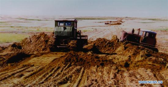 File photo shows people building a road at the Kubuqi Desert in 1990s, in Hangjin Banner, north China's Inner Mongolia Autonomous Region. Kubuqi, the seventh largest desert in China, is a good example of China's success in alleviating desertification. About 6,460 square kilometers of the Kubuqi desert has been reclaimed in the last 30 years. (Xinhua)