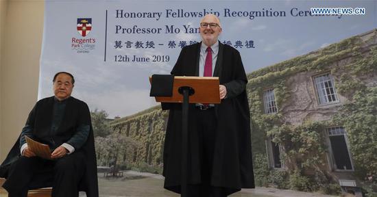 Regent's Park College principal Robert Ellis (R) speaks during the Honorary Fellowship Recognition Ceremony of Chinese writer and Nobel laureate Mo Yan at University of Oxford, Britain, on June 12, 2019. Mo Yan was awarded Wednesday the Honorary Fellowship by Regent's Park College, University of Oxford, in recognition of his contribution to Chinese and world literature. The college principal Robert Ellis presented the gown and stole to Mo at the ceremony. They unveiled together a new international writing center named after Mo. (Xinhua/Han Yan)