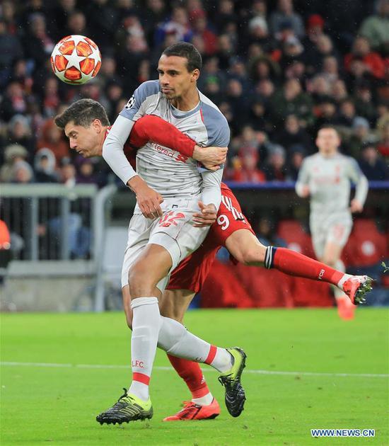 Liverpool's Joel Matip (front) vies with Bayern Munich's Robert Lewandowski during the UEFA Champions League 1/8 finals second leg match between Bayern Munich of Germany and Liverpool of England in Munich, Germany, on March 13, 2019. Liverpool won 3-1 and advanced into the quarterfinals. (Xinhua/Philippe Ruiz)