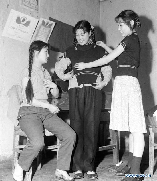 Women with braids try on sweaters at a knitting factory in Urumqi, northwest China's Xinjiang Uygur Autonomous Region, April 20, 1961. Along with China's reform and opening-up starting from 1978, Chinese women have refreshed their images year after year, which can be simply seen from their hairstyles. Women's hairstyles, just like a mirror, reflect fashion changes and most importantly, Chinese women's increasingly diversified definition of beauty. (Xinhua)