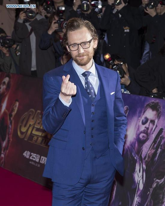 Tom Hiddleston crosses his fingers to form a heart shape to fans during a promotion event of