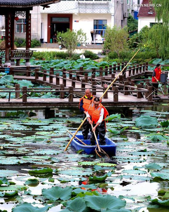 Volunteers clear the surface of a pond in Xucang Village, Changxing County of east China's Zhejiang Province, Sept. 21, 2020. Local authorities launched a campaign to clear up the water system in villages to secure a pleasant environment. (Xinhua/Xu Yu)