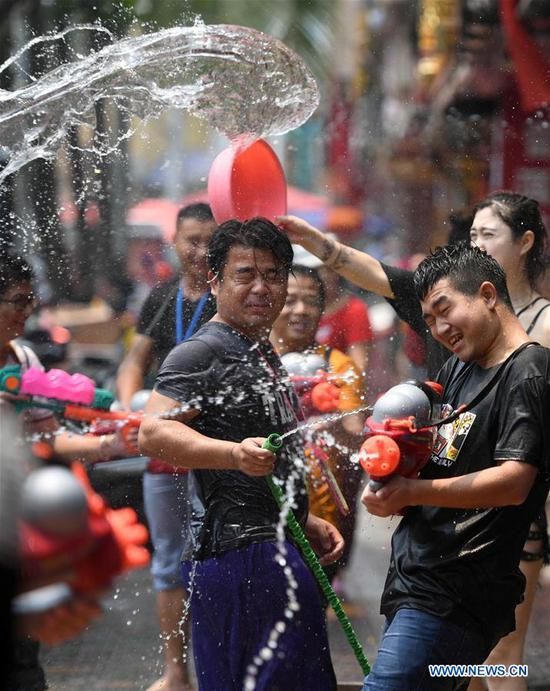 People celebrate the water-sprinkling festival on a street in Jinghong City, Dai Autonomous Prefecture of Xishuangbanna, southwest China's Yunnan Province, April 15, 2019. People sprinkle water to each other to pray for good fortune during the traditional water-sprinkling festival, which is also the New Year festival of the Dai ethnic group. (Xinhua/Qin Qing)