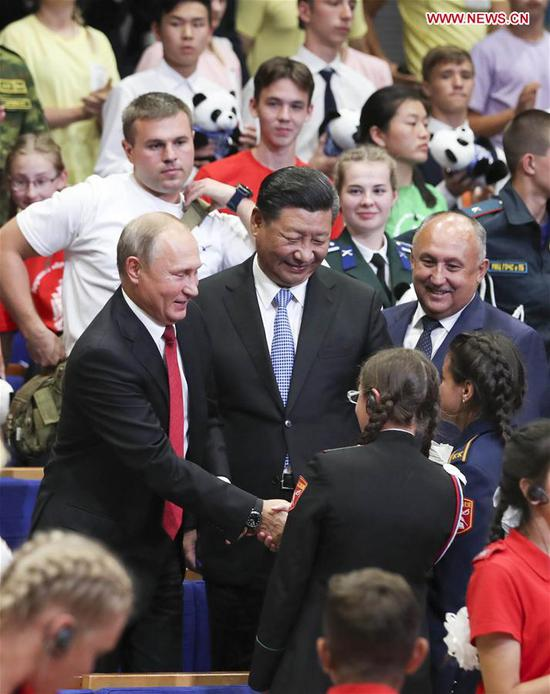 """Chinese President Xi Jinping and Russian President Vladimir Putin talk with children at the All-Russian Children's Center """"Ocean"""" while attending commemoration events marking the 10-year anniversary of the center's hosting of hundreds of Chinese children from regions hit by a deadly earthquake in 2008, in Vladivostok, Russia, Sept. 12, 2018. (Xinhua/Xie Huanchi)"""