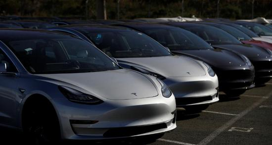 FILE PHOTO: A row of new Tesla Model 3 electric vehicles is seen at a parking lot in Richmond, California, U.S. June 22, 2018.