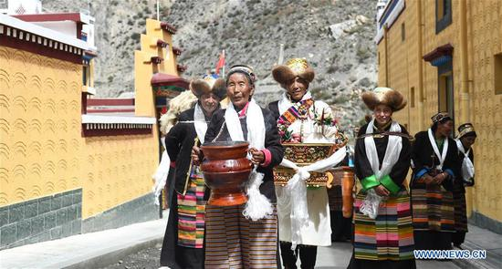 Dainzin Quzhen (front) holds a traditional rite with family members before moving into her new house in Lhozhag Town of Lhozhag County, Shannan City, southwest China's Tibet Autonomous Region, Sept. 21, 2019. A total of 88 villagers from 28 households moved to their new two-story dwellings to improve housing conditions. (Xinhua/Jigme Dorje)
