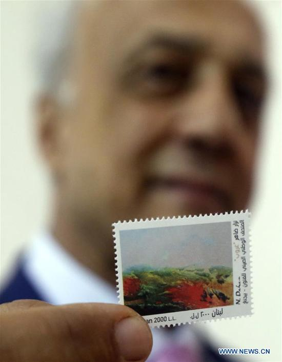 Lebanese artist Nizar Daher shows a stamp made of his painting