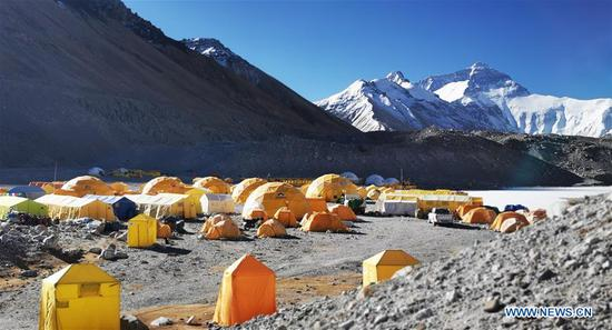 Photo taken on April 29, 2019 shows the base camp of the northern face of Mount Qomolangma in southwest China's Tibet Autonomous Region. Every year, for a few weeks, hundreds of climbers and supporting personnel come to the base camp of the northern face of Mount Qomolangma, trying to reach the summit of the tallest and most famous mountain in the world. Before starting climbing, they need to hike several times between elevations from 5,000 meters to 7,000 meters, giving their bodies some time to adapt. When this process is over, it's all up to the weather. The base camp is a popular place to wait for the window. Among the six camps on the northern face, the base camp at an altitude of 5,200 meters is the furthest cars can reach and therefor the most equipped. Besides food and accommodation, climbers can also enjoy tea and massage. They can also play football on perhaps the highest field. There's even a simple gym in the camp. Environmental protection is a priority here. Garbage sacks are given to each climbing team. Special containers are put in every camp to collect trash and sewage. The collected trash must be treated 100 kilometers away, and the only road is a zigzagging track. It is not trucks, but yaks that are generally used to make the journey. Actually yaks are vital on the mountain. Beyond the base camp, yak is the only reliable transport. (Xinhua/Zhaxi Tsering)