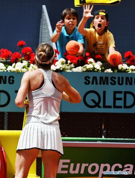 Simona Halep of Romania throws her towel to two kids after the women's individuals round 16 match against Kristyna Pliskova of the Czech Republic at the Madrid Open Tennis tournament in Madrid, Spain, May 9, 2018. Simona Halep won 2-0. (Xinhua/Guo Qiuda)