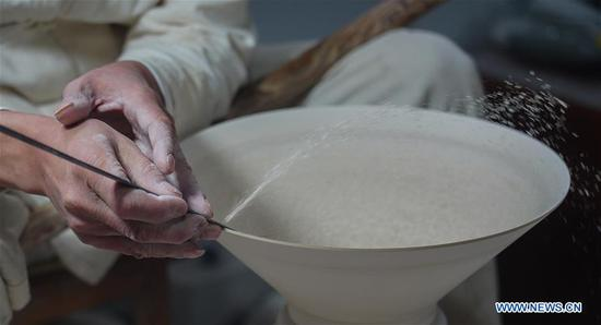 Xiong Guoan trims an unburnt porcelain bowl in Jingdezhen, east China's Jiangxi Province, Oct. 28, 2019. Xiong Guoan, an inheritor of thin body porcelain in Jingdezhen of Jiangxi, learnt the art from his father when he was 12 years old. Working in the field for 47 years, he insists for perfection in the making procedures. The shaping of the unburnt porcelain is the essence of the craft, during which craftsman will use tools to peel the unburnt porcelain until it can be penetrated by the light. Xiong's skill has allowed him to make thin body porcelain with a thickness of about 0.15 millimeter. (Xinhua/Zhou Mi)