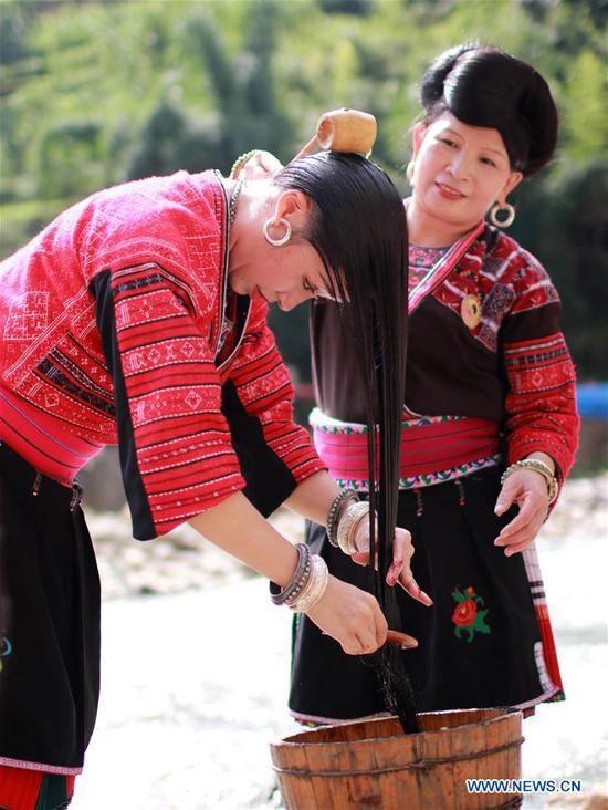Women wash their long hair along the riverside in Huangluo Village of the Yao ethnic group in Longji Township of Longsheng County, south China's Guangxi Zhuang Autonomous Region, July 4, 2019. Women here have the tradition of keeping long hair. They use fermented rice water- the water after rinsing rice- together with natural ingredients such as tea seeds and orange peels to wash their hair. The natural shampoo keeps their hair healthy, smooth and shiny. (Photo by Liu Jiaoqing/Xinhua)
