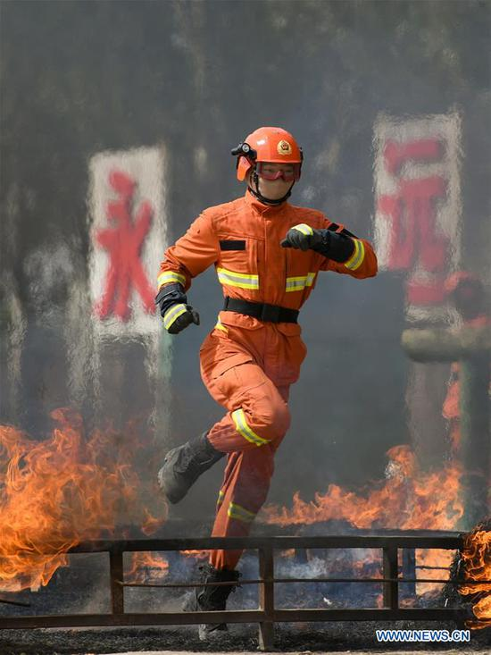 A newly-recruited fireman leaps over a fire barrier during a training in Hohhot, north China's Inner Mongolia Autonomous Region, June 5, 2019. Over 1,100 socially-recruited firemen are receiving a six-month training in Hohhot. (Xinhua/Peng Yuan)