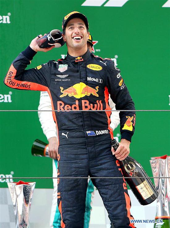 Red Bull's driver Daniel Ricciardo of Australia celebrates with his shoe on the podium after winning the Formula One Chinese Grand Prix in Shanghai, east China, April 15, 2018. Daniel Ricciardo claimed the title of the event in 1 hour, 35 minutes and 36.380 seconds. (Xinhua/Fan Jun)